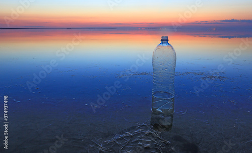 Photo Plastic bottle in water on sunset background