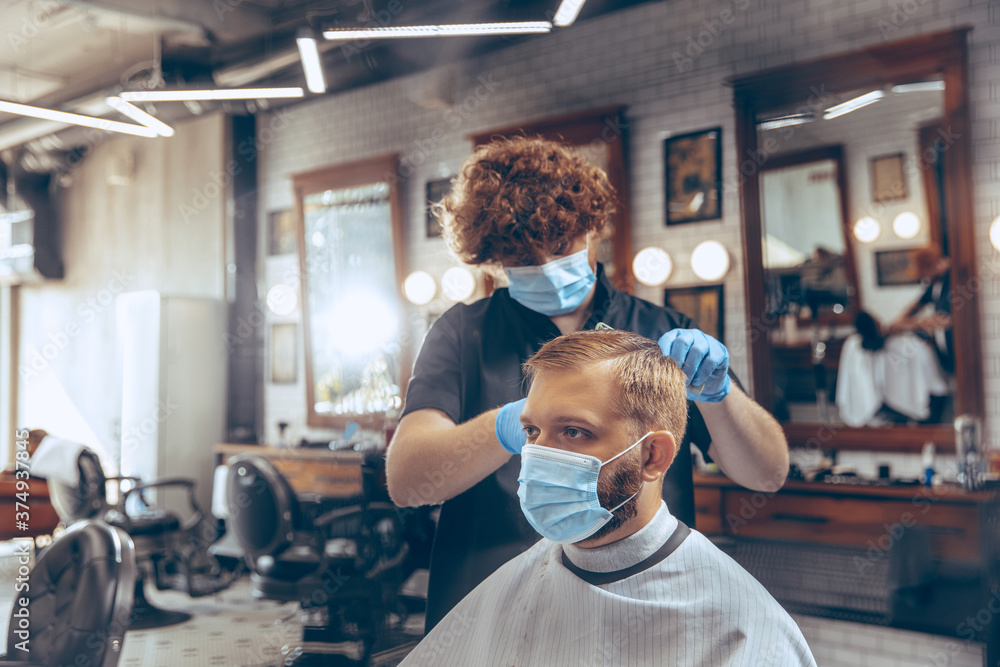 Fototapeta Man getting hair cut at the barbershop wearing mask during coronavirus pandemic. Professional barber wearing gloves. Covid-19, beauty, selfcare, style, healthcare and medicine concept.