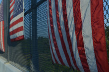 Vertical Stripes In Flag In Row Of American Flags On Fence Of Highway Overpass