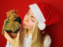 Portrait Of Young Woman Wearing Santa Hat And Holding Present