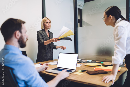 Photo Colleagues having argument about paperwork in office room
