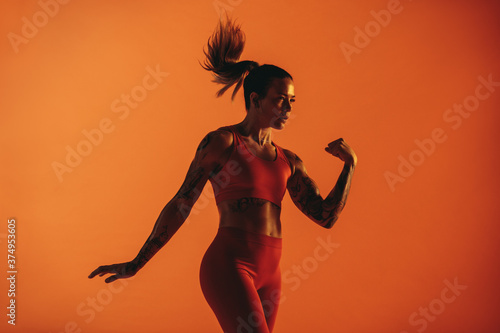 Portrait of female athlete with tattoo on arms