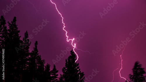 Photo Bright bolt lightning in the dark purple sky against the forest background