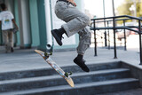 Young boy riding trick on skateboard in city