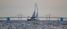 Panoramic Image Of A Sailboat Moving Across Chesapeake Bay With The Silhouette Of The Famous Bay Bridge In The Background. There Are People On The Boat Who Are Enjoying The Sunset Over The Bay,.