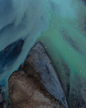 Aerial View Of Beautiful Blue And Green Patterns, And Swans Swimming In The Water Of Glacial River Héraosvotn In North Iceland.