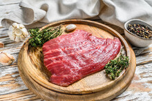 Raw Flat Iron Steak On A Cutting Board. Fresh Marble Beef Meat Black Angus. White Wooden Background. Top View