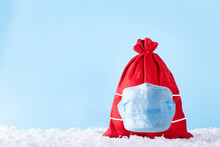Red Christmas Present Bag With Gifts In Protective Medical Mask On Snow Over Blue Background