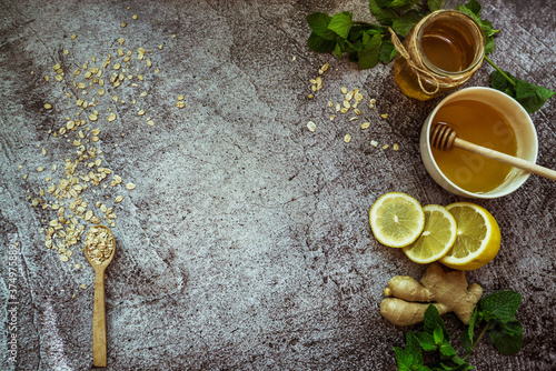 Photo honey, lemon, mint, ginger, oatmeal with a spoon - home remedy to prevent colds