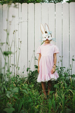 Child Wearing Her Homemade Bunny Mask With Blade Of Grass In Her Mouth