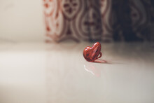 Plastic Red Heart Shaped Ring Sitting On White Desk