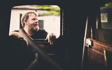 Bearded Man Looking Inside Window Of Vintage Truck