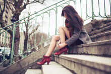 Attractive Woman Ties Her Red Shoes