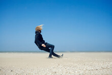 Young Man Leaning Against The Strong Wind On The Beach And Falls Down