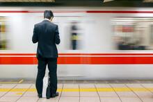Asia, Japan, Honshu, Tokyo, Tokyo Subway, Business Man In Front Of Passing Subway Train - Blurred Motion