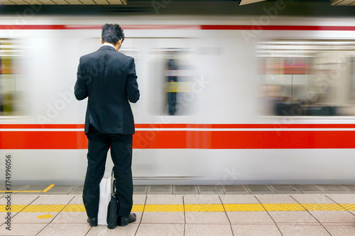 Asia, Japan, Honshu, Tokyo, Tokyo Subway, business man in front of passing subway train - blurred motion