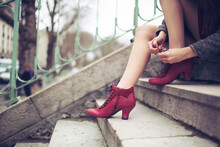 Woman Ties Her Red Shoes