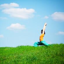 Young Woman Doing Yoga In Natu...