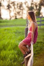 Young Woman Sitting On Paddock Fence In Pasture