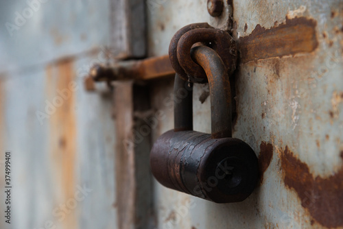 Photo old rusty lock on the door in an abandoned house close-up