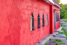 Beautiful Red Wall Of The Building. Red Building With Unusual Windows. Windows With Interesting Bars.