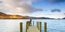 Derwent Water, Lake District National Park, Cumbria, England, UK - Fisherman On The Wooden Jetty At Barrow Bay Landing
