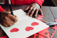 Black Girl's Hand Writing A Valentine's Day Card