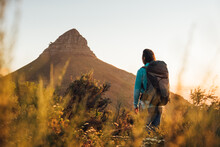 Woman With Back Hiking In The Mountains At Sunset