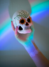 Painted Sugar Skull Being Help Up Against A Prism