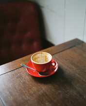 Empty Red Coffee Cup And Saucer On A Wooden Table In A Cafe.