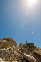 A Man Stans Atop A Rocky Outcrop, With Seagulls Flying Above Him