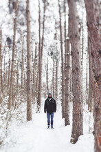 Young Man Standing On Snowy Forest Path