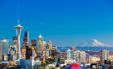 Characteristic Horizontal View Of Downtown Seattle With Space Needle And Mount Rainier At Sunset