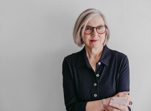 Portrait Of Mature Woman Wearing Glasses And Using Mobile Phone On Seamless White Studio Background