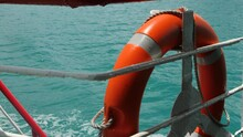 Ring Buoy Red Color On Ferry Ship. Marine Sea Wave Water Background