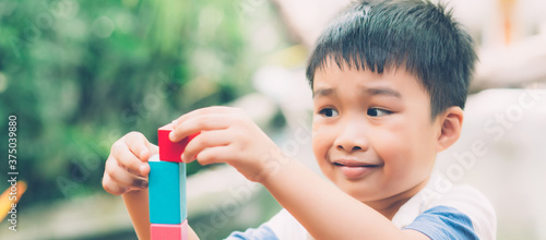 Asian young boy playing wooden block toy on table for creative and development, happy child learn skill for activity puzzle and creativity for game on desk at home, education concept, banner website Fototapet