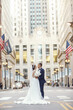 canvas print picture - Elegant bride in a white dress and veil. Handsome groom in a blue suit. Couple in a big city