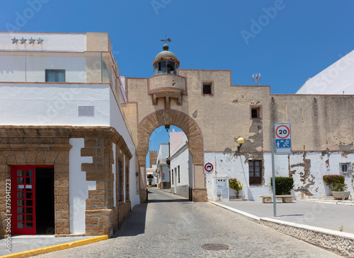 White buildings at the port of the Spanish city of Rota. In the middle is an archway with an old beacon and a narrow alley with a tower at the end.