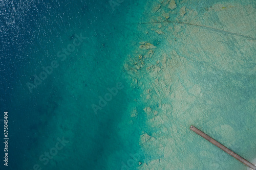 pier on tropical island and turquoise clear water. High altitude aerial view of a wooden pier on turquoise transparent water. Copy space.