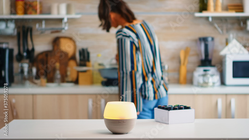 Obraz Essential oils diffuser distributing aromatherapy while woman walks in the kitchen. Aroma health essence, welness aromatherapy home spa fragrance tranquil theraphy, therapeutic steam, mental health - fototapety do salonu