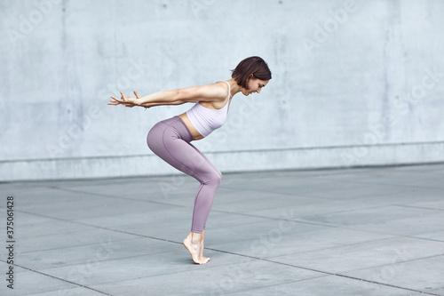 Frau/Mädchen in Pastell gekleidet macht Outdoor Yoga Übungen/Sonnegruß in moderner Beton Architektur Canvas Print