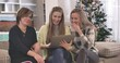 Three positive Caucasian women sitting on couch and using laptop. Portrait of smiling friends spending Christmas weekends indoors. New Year eve, holidays season. Cinema 4k ProRes HQ.