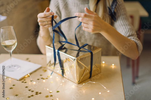 Young woman opening her present wrapped in gold paper. Tapéta, Fotótapéta
