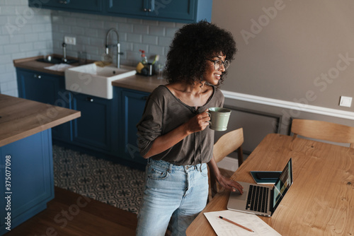 Obraz Smiling young female entrepreneur working on laptop - fototapety do salonu