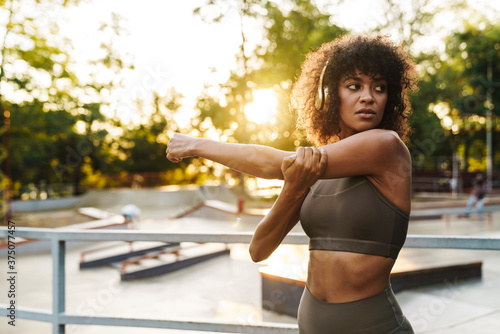 Foto Image of african american sportswoman doing exercise on sports ground