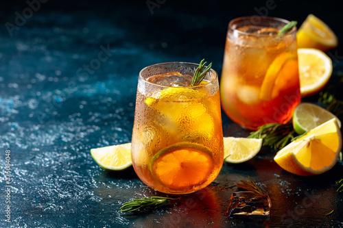 Fototapeta Iced tea with lemon, lime and ice garnished with rosemary. obraz