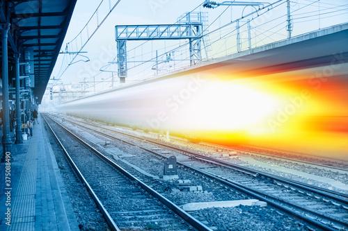 Fototapeta High speed train runs on rail tracks - Train in motion