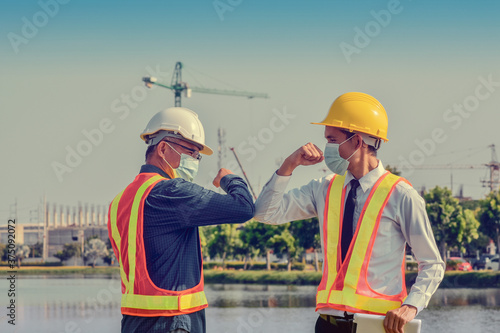 Fototapeta Engineers saluting each other by touching elbows,Two business people shake hand no touch outdoor on site construction obraz