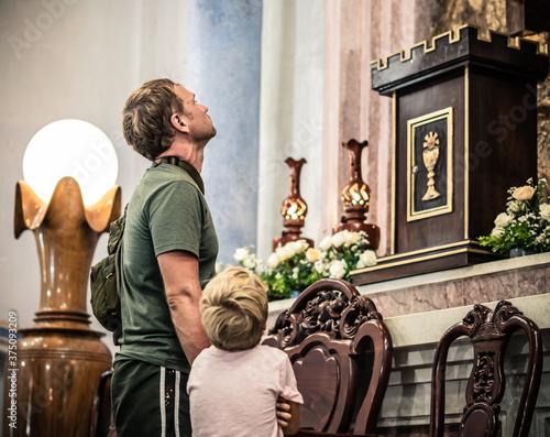 Fotografiet Christian dad tells boy Bible stories standing near Saint Jesus statue