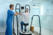 Man On Special Simulator And Observing Rehabilitation Therapist